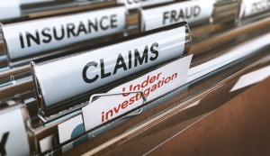 "Close up photo of a file of folders named ""Claims"", ""Insurance"" and ""Fraud"""